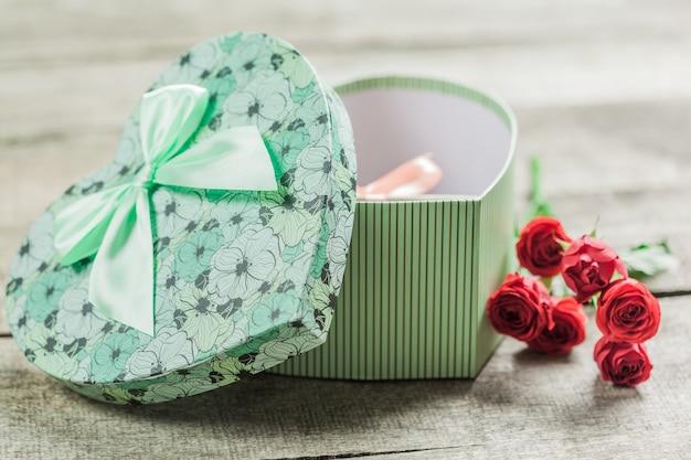 Rose e cuori sul bordo di legno, fondo di giorno di biglietti di s. valentino
