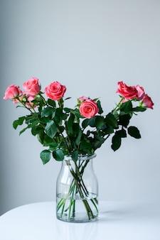 Rose in un vaso trasparente su uno sfondo grigio con spazio per il testo.
