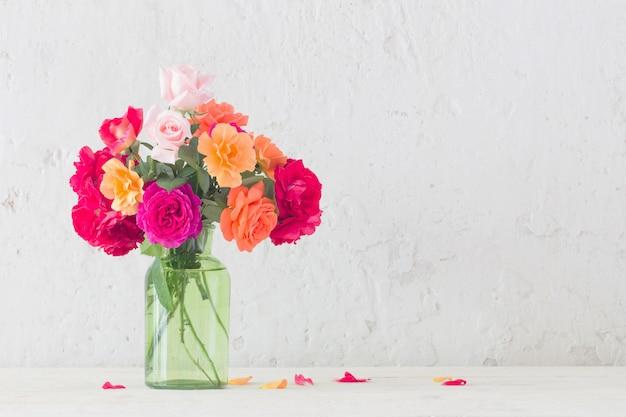 Rose in vaso sul muro bianco