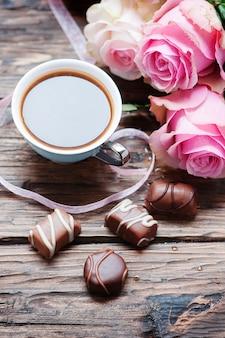 Rose rosa, caffè e cioccolato sul tavolo di legno