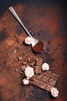 Rose rosa con barra di cioccolato e sciroppo su sfondo scuro con texture