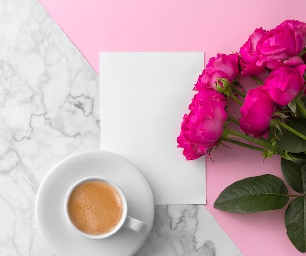 Rose rosa con biglietto di auguri in bianco e tazza di caffè su marmo rosa