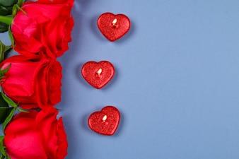 Rose rosa con candele rosse a forma di cuore. 8 marzo, festa della mamma, San Valentino.
