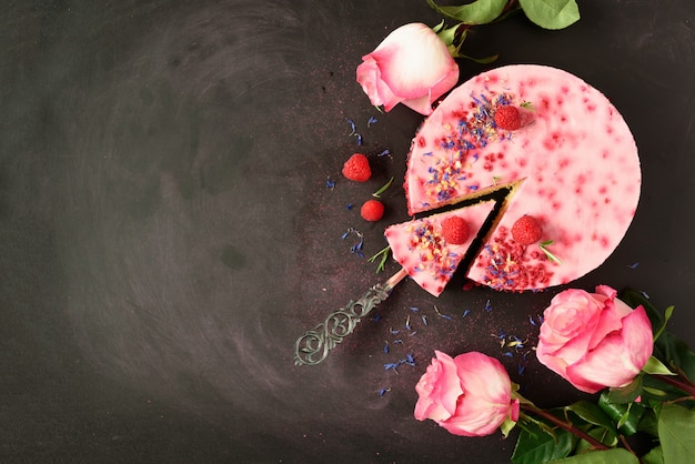 Rose rosa e deliziosa torta di lamponi con bacche fresche, rosmarino, fiori secchi. vegetariano, concetto di cibo vegano