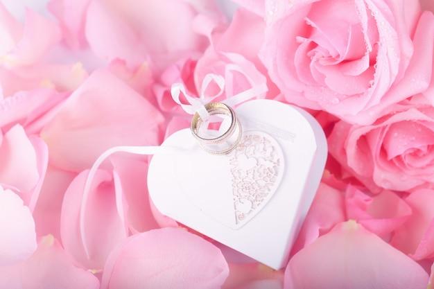 Rose rosa e fedi nuziali a forma di cuore
