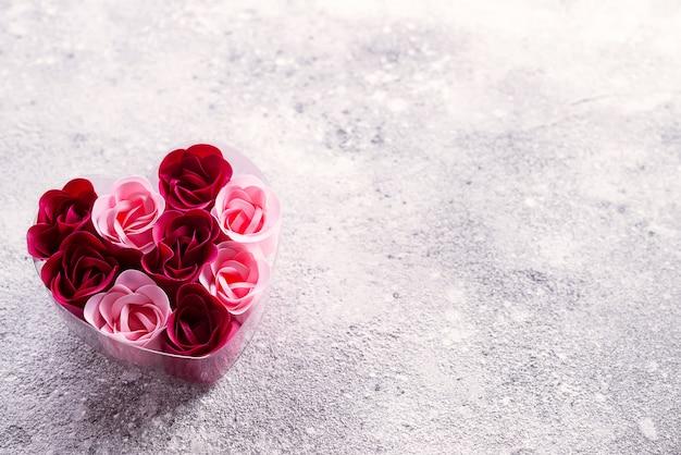 Rose rosa e rosse brillanti fatte di scaglie di sapone, in una scatola a forma di cuore.