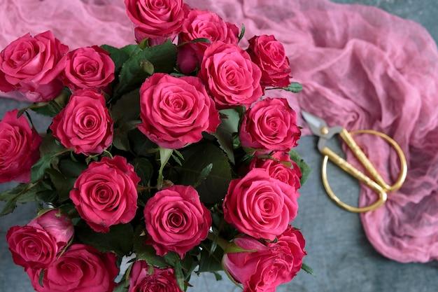Rose rosa in un vaso sul tavolo e forbici floreali