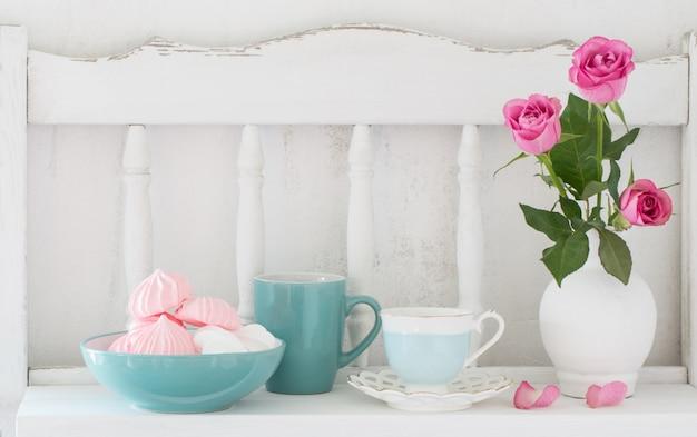 Rose rosa in vaso e stoviglie sullo scaffale di legno bianco