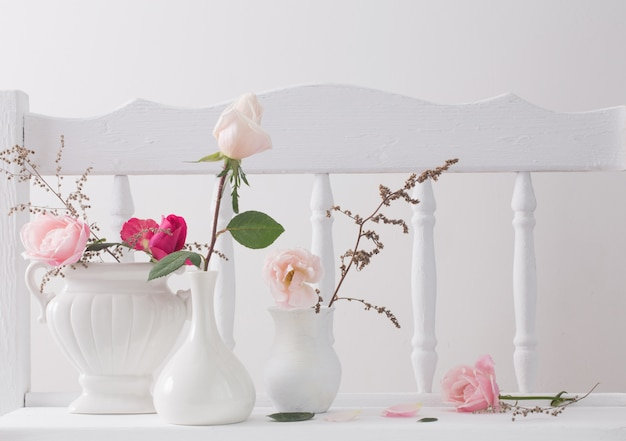 Rose rosa sullo scaffale bianco di legno d'annata