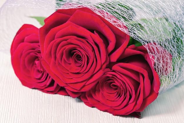Rose rosse avvolte nella griglia bianca su fondo di legno con copyspace. bouquet di fiori che sbocciano. messa a fuoco selettiva.