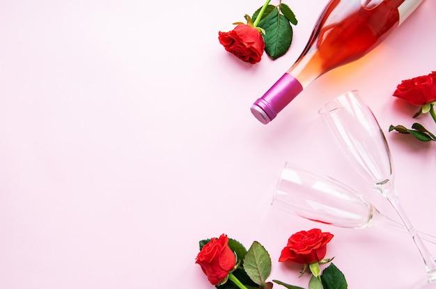 Rose rosse, bicchieri e bottiglia di vino