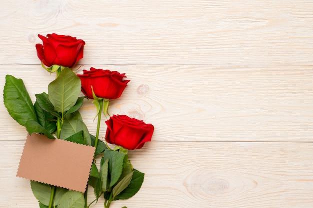 Rose rosse con carta di carta artigianale vuota sul tavolo rustico, congratulazioni per il giorno delle donne