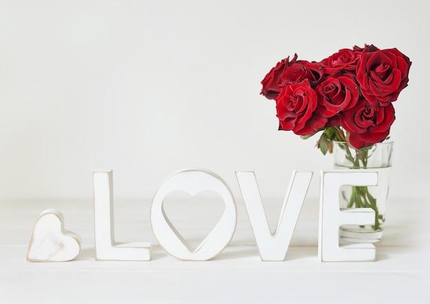 Rose rosse con cuore, lettere in legno amore, modello di cartolina