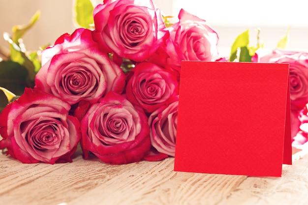 Rose rosse con la cartolina d'auguri rossa in bianco per il giorno di biglietti di s. valentino