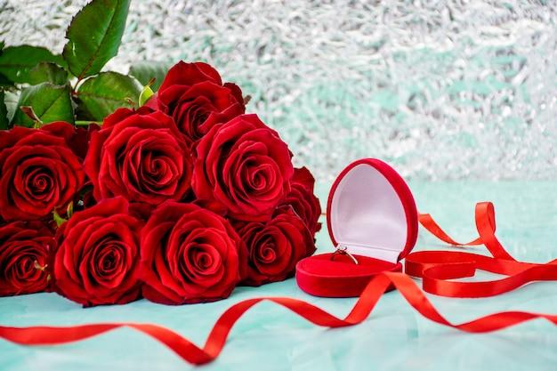 Rose rosse con sfondo boke. scatola con un anello. fiocco rosso.