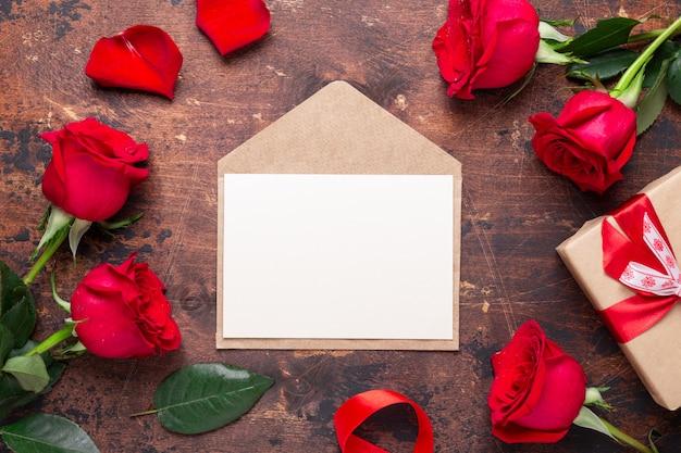 Rose rosse, confezione regalo e busta su fondo di legno