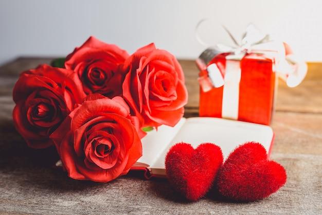 Rose rosse, cuore rosso, taccuino e contenitore di regalo su un fondo di legno