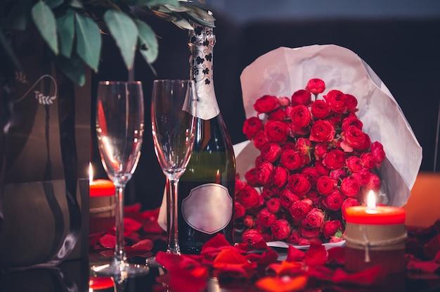 Rose rosse, due bicchieri, bottiglia di champagne e candela sul tavolo