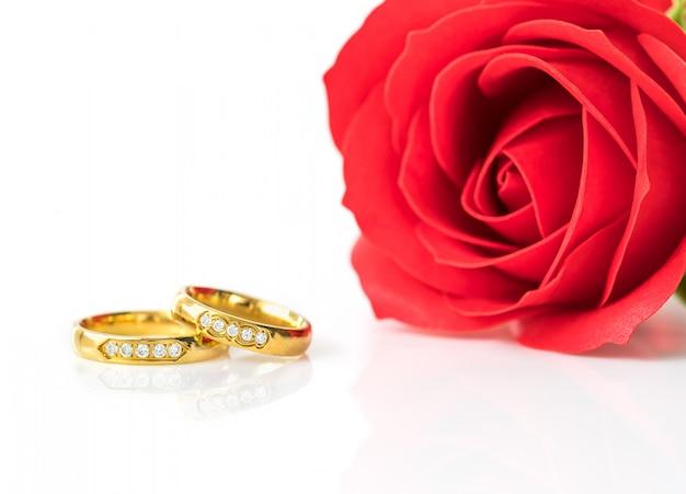 Rose rosse e anelli d'oro su bianco