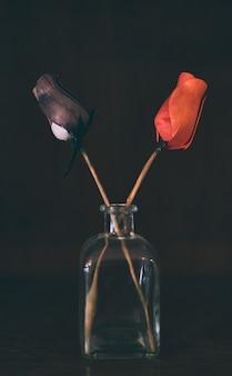 Rose rosse e nere in un barattolo di vetro su uno sfondo scuro