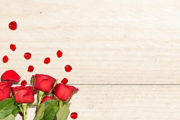 Rose rosse e petali di rosa su un tavolo di legno
