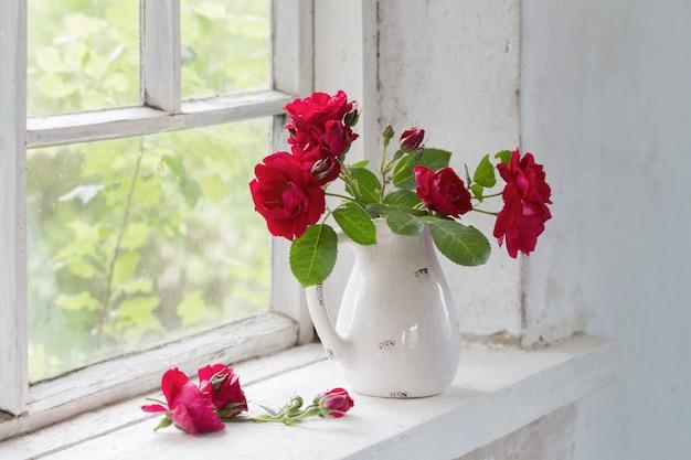 Rose rosse in brocca su winwowsill