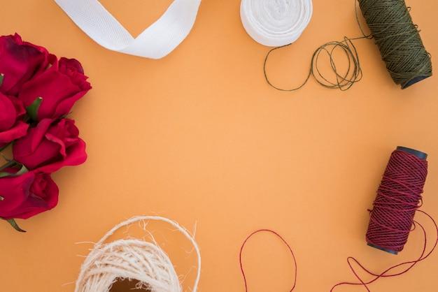 Rose rosse; nastro bianco; rocchetto di filo su sfondo colorato