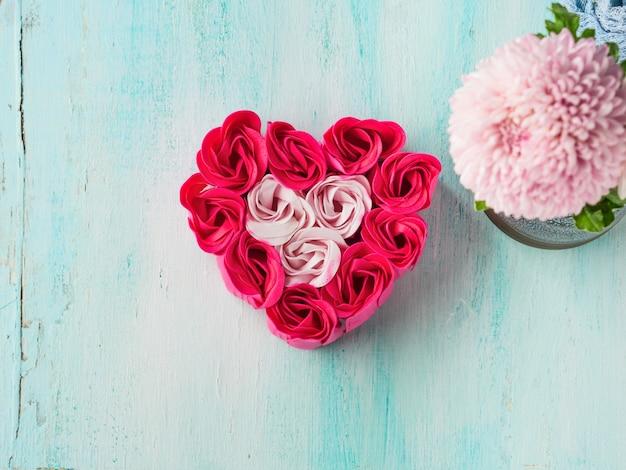 Rose rosse rosa a forma di cuore su colore pastello