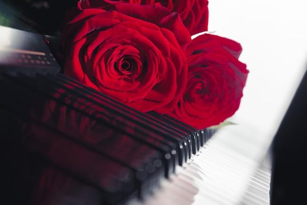 Rose rosse sui tasti del pianoforte