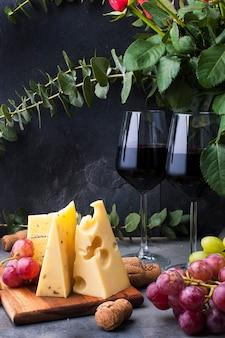 Rose rosse, uva, formaggio e un bicchiere di vino rosso su uno sfondo di cemento nero
