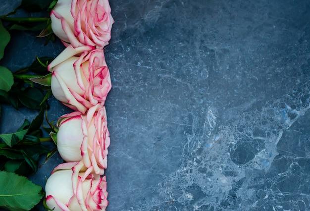 Rose su fondo di marmo scuro con posto per testo. distesi