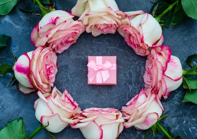 Rose su fondo di marmo scuro con posto per testo. pacco regalo. distesi