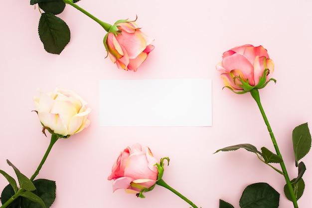 Rose sul rosa con un biglietto di auguri vuoto