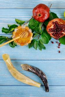 Rosh hashanah tovah concetto. tavolo blu con melograno, miele e corno.