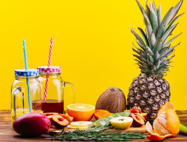 Rosmarino; noce di cocco; la frutta ed il succo in barattolo di muratore aggrediscono sulla tavola di legno contro fondo giallo