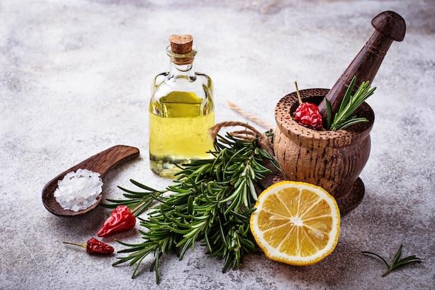Rosmarino, sale, limone, olio e pepe. varie spezie su sfondo concreto. messa a fuoco selettiva