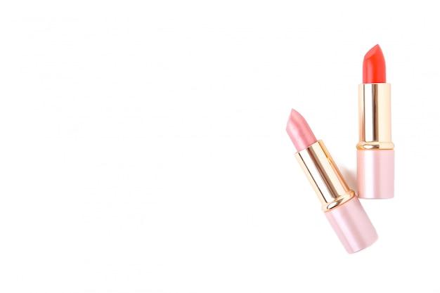Rossetto rosso e rosa isolato su sfondo bianco