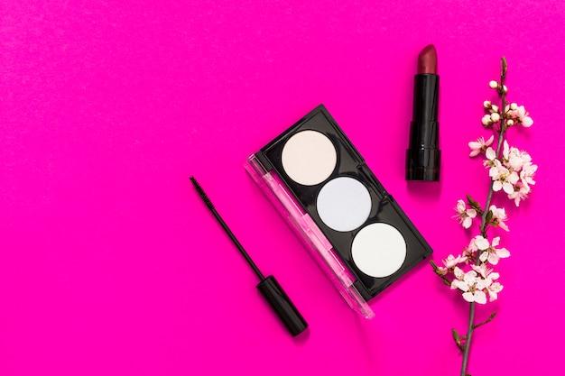 Rossetto rosso; ombretto; pennello mascara e ramoscello di fiori su sfondo rosa