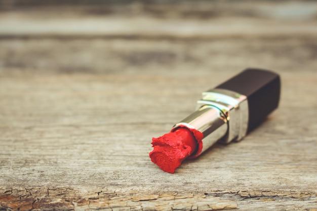 Rossetto rosso rotto su legno vecchio