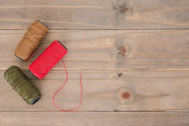 Rosso; bobina di filo marrone e verde sul tavolo di legno