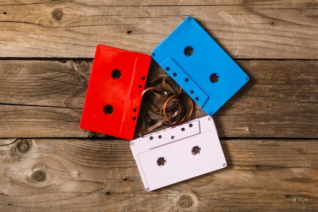 Rosso; cassette bianche e blu con nastro aggrovigliato su fondo in legno