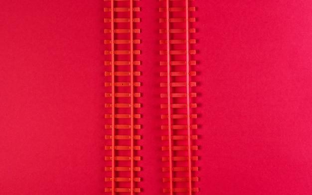 Rotaie ferroviarie del giocattolo su una tavola rossa.