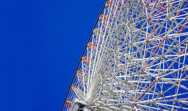 Rotella di ferris gigante di tempozan del raccolto e del primo piano su cielo blu luminoso