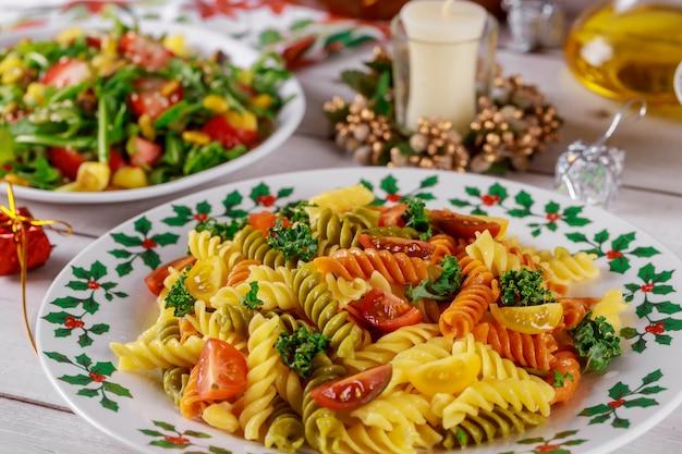 Rotini di pasta colorata, pomodorini sul tavolo di natale con insalata