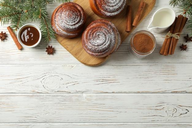 Rotoli di cannella, caramello, latte e rami di abete sul tavolo di legno bianco