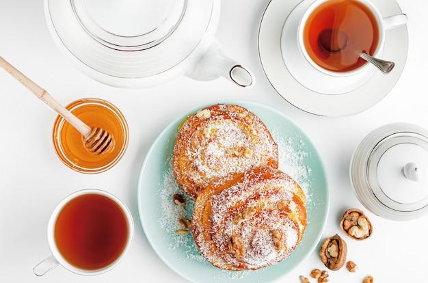 Rotoli di cannella casalinghi dolci con tè e miele su bianco. vista dall'alto.
