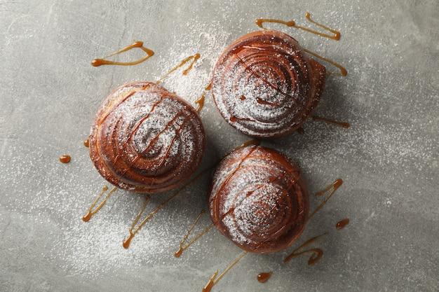 Rotoli di cannella con caramello e zucchero a velo su gray