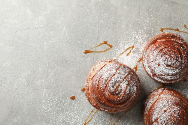 Rotoli di cannella con caramello e zucchero a velo sulla tavola grigia