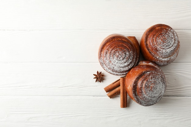 Rotoli di cannella con lo zucchero a velo e le pile di cannella su di legno bianco