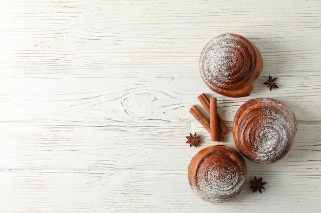 Rotoli di cannella con zucchero a velo e bastoncini di cannella su bianco in legno